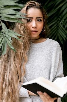 Kobieta pozuje za niektóre liśćmi podczas gdy trzymający książkę