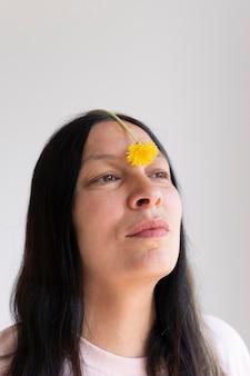 Kobieta pozuje zmysłowo z kwiatem