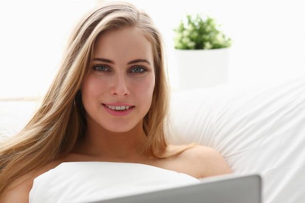 Kobieta praca winh laptopa zatrzymać się w łóżku wcześnie rano