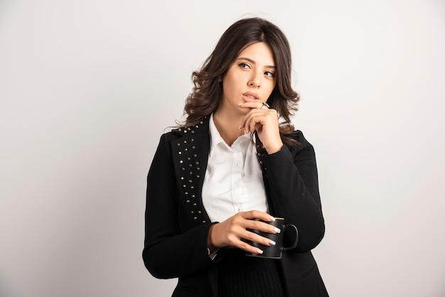Kobieta pracownik biurowy pozuje z filiżanką herbaty na białym
