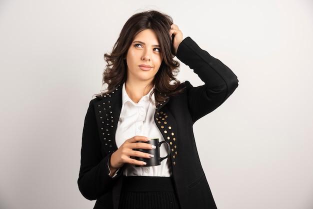 Kobieta pracownik biurowy pozuje z filiżanką herbaty