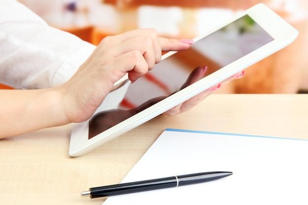 Kobieta pracownik biurowy za pomocą cyfrowego tabletu w kawiarni