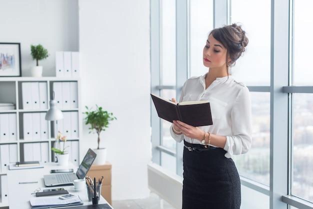 Kobieta pracownik biurowy zapisywanie notatek i planu dnia w swoim notesie, stojąc w miejscu pracy, portret widok z przodu.