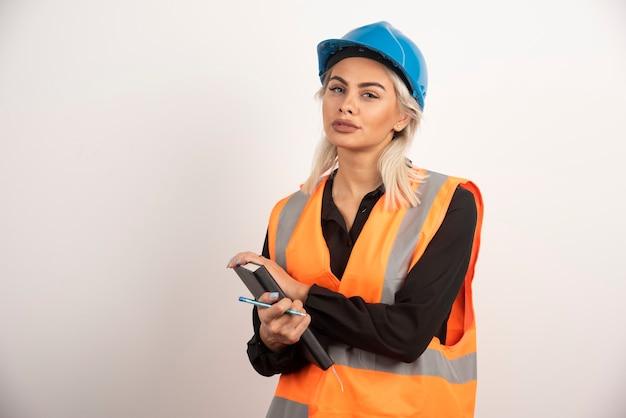 Kobieta pracownik budowlany pozycja z notatnikiem. wysokiej jakości zdjęcie