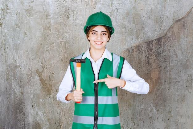 Kobieta pracownik budowlany w zielonym kasku trzymając młotek i dając znak ok