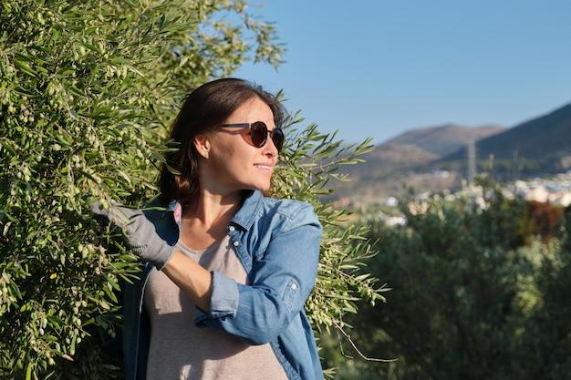 Kobieta pracownik farmy oliwek, tło ogród oliwny w górach