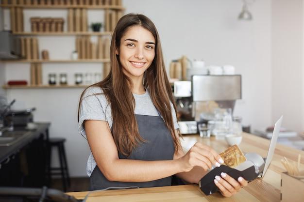 Kobieta pracownik kawiarni za pomocą czytnika kart kredytowych wystawiać rachunek na klienta patrząc szczęśliwy uśmiechając się do kamery.