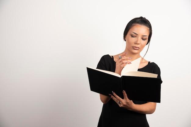 Kobieta pracownik patrząc na notatki na białej ścianie.