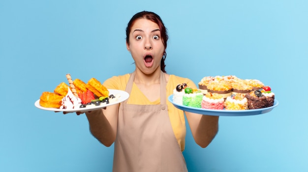 Kobieta pracownik piekarni tty z goframi i ciastami