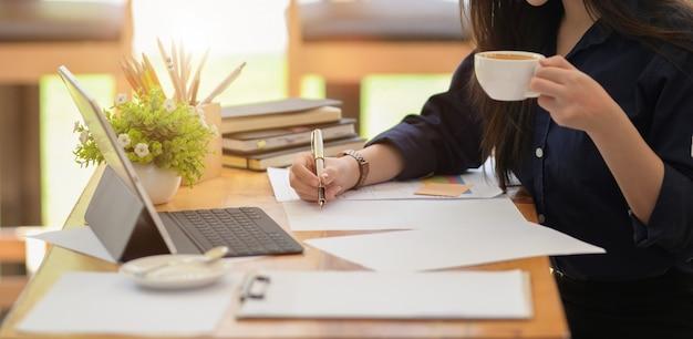 Kobieta pracownik pracuje z papierowymi pracami i laptopem