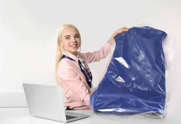 Kobieta pracownik pralni trzymając czyste ubrania w recepcji