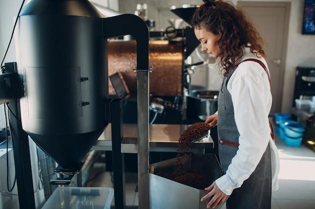 Kobieta pracownik przy maszynie do usuwania kamienia w procesie palenia kawy