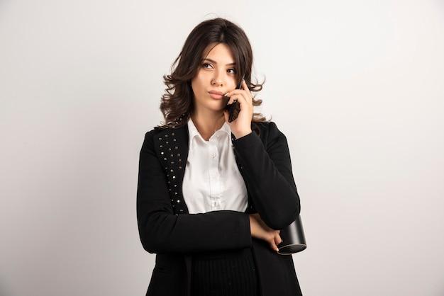 Kobieta pracownik rozmawia przez telefon na białym