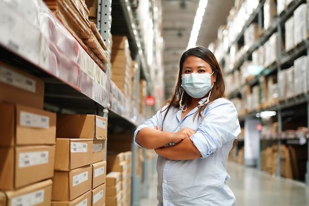Kobieta pracownik sprawdzający stan zapasów produktów podczas pracy w dużym magazynie.