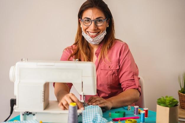 Kobieta pracownik używa szwalną maszynę podczas gdy robić twarzy medycznym maskom