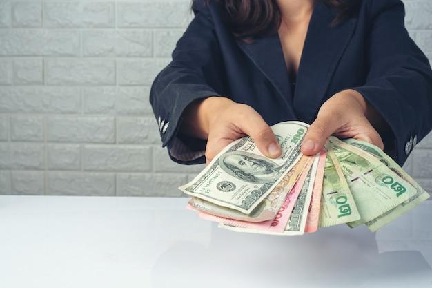 Kobieta pracowników liczenie pieniędzy na białym biurku