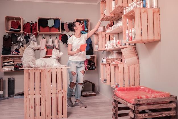 Kobieta pracująca. ciemnowłosa kobieta w dżinsach i koszulce kochająca zwierzęta pracująca w sklepie dla zwierząt domowych