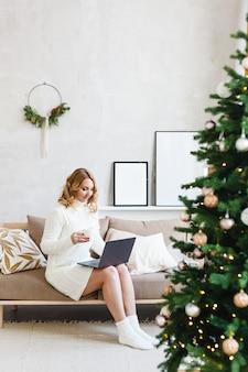 Kobieta pracująca lub studiująca na komputerze, wnętrze jest urządzone na boże narodzenie