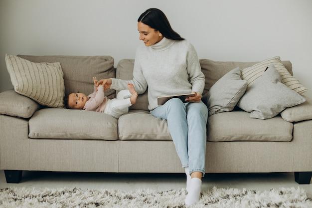 Kobieta pracująca na komputerze i siedząca na kanapie ze swoją córeczką