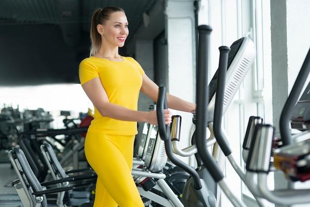 Kobieta pracująca na maszynie eliptycznej w siłowni