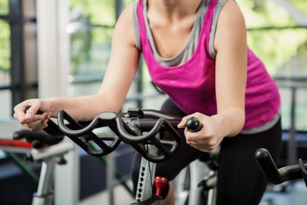 Kobieta pracująca na rowerze stacjonarnym w spinning klasy