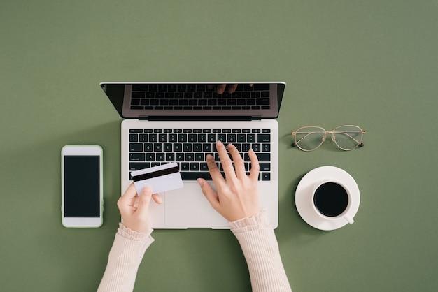 Kobieta pracująca przy biurku i kupująca produkty online, dokonuje płatności kartą kredytową
