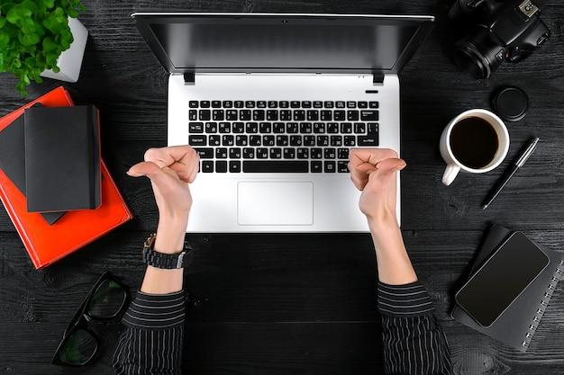 Kobieta pracująca przy stole w biurze. widok z góry ludzkich rąk, klawiatury laptopa, filiżanki kawy, smartfona, notebooka i kwiatka na tle drewniany stół.