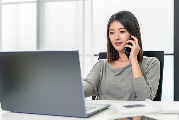 Kobieta pracująca rozmawia przez telefon komórkowy