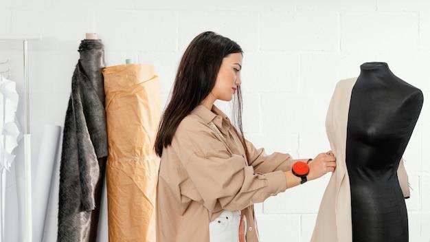 Kobieta pracująca sama w swoim warsztacie projektowania mody