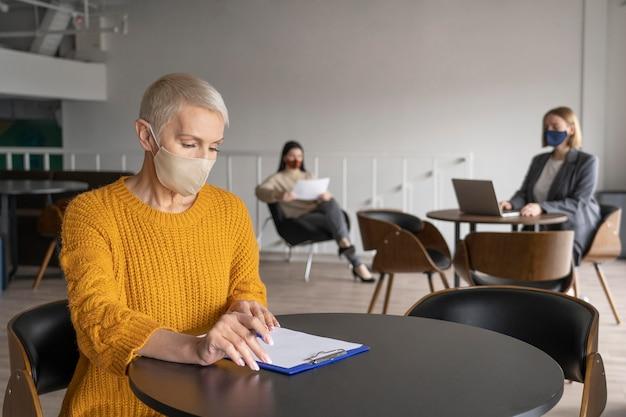 Kobieta pracująca samotnie z dystansem społecznym od innych współpracowników