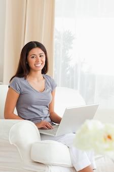 Kobieta pracująca siedzi na kanapie z notebooka, patrząc na kamery