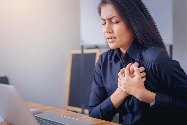 Kobieta pracująca stawia czoło cierpienia i trzyma piersi z powodu zawału serca w biurze