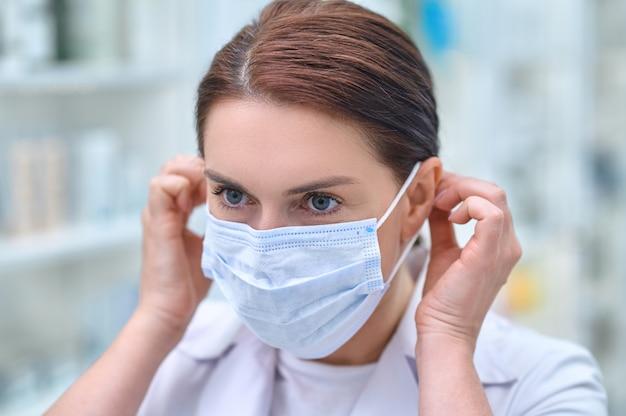 Kobieta pracująca w aptece zakłada maskę ochronną