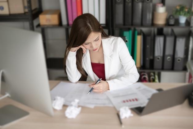 Kobieta pracująca w białym garniturze myśli o nowym projekcie.