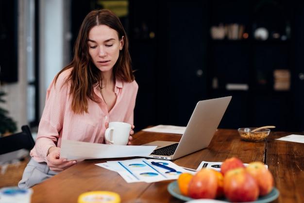 Kobieta pracująca w domowym biurze siedzi przy biurku analizując statystyki biznesowe trzymając diagramy i wykresy za pomocą laptopa.