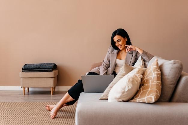 Kobieta pracująca w domu na laptopie z powodu kwarantanny, siedząca na sofie