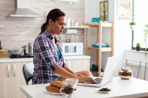 Kobieta pracująca w domu przy użyciu laptopa w kuchni podczas śniadania
