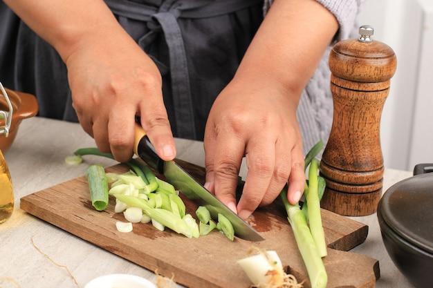 Kobieta pracująca w kuchni do krojenia warzyw. kobieta krojenie dymki na sałatkę. zbliżenie szefa krojenia cebuli.