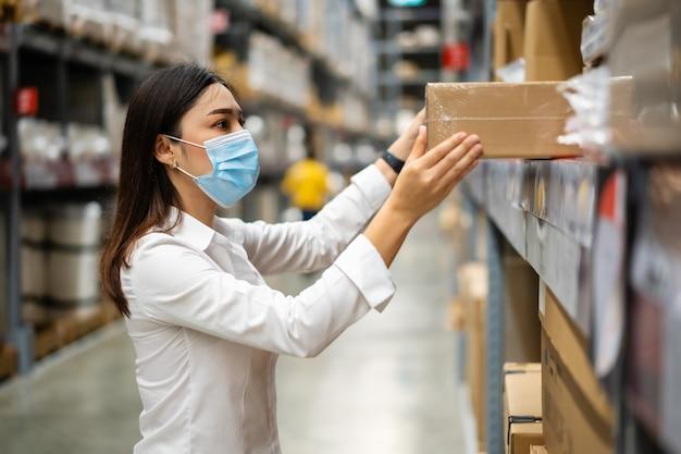 Kobieta pracująca w masce medycznej sprawdzająca stan magazynu podczas pandemii koronawirusa