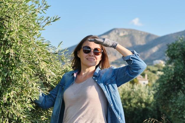 Kobieta pracująca w ogrodzie oliwnym, tło górskie, słoneczny jesienny dzień