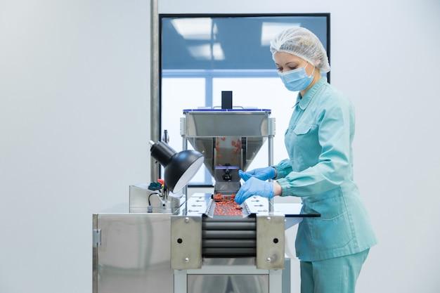 Kobieta pracująca w przemyśle farmaceutycznym w odzieży ochronnej obsługująca produkcję tabletek w sterylnych warunkach pracy