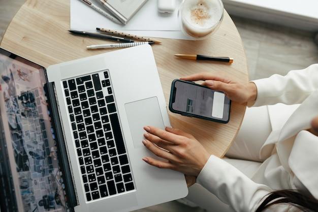 Kobieta pracująca w ręce laptopa z bliska. zbliżenie kobiece ręce zajęty pisaniem na laptopie. pracować w domu. koncepcja kwarantanny i dystansu społecznego.