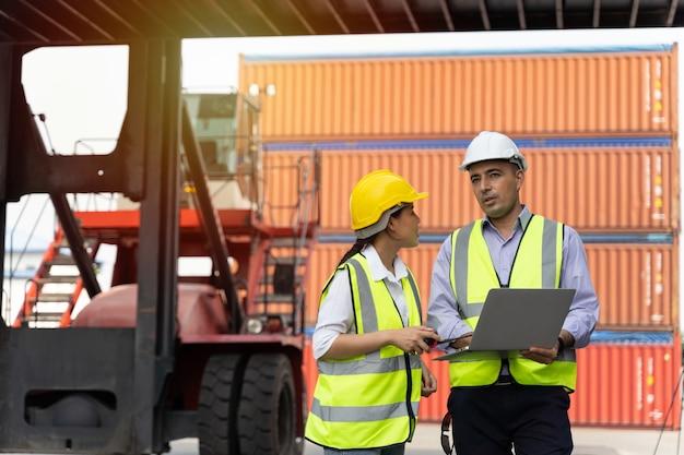 Kobieta pracująca z brygadzistą, stojąca z żółtym hełmem, aby kontrolować załadunek i sprawdzać jakość kontenerów ze statku towarowego cargo do importu i eksportu w stoczni lub porcie
