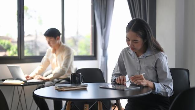 Kobieta pracująca z cyfrowym tabletem siedząc z kolegą w biurze.