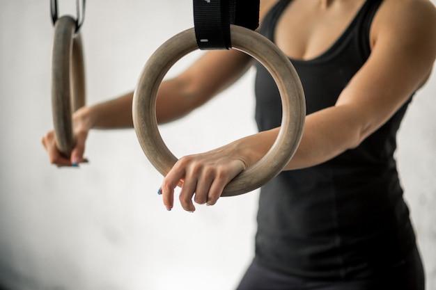 Kobieta pracująca z gimnastycznymi pierścionkami przy cross fit gym
