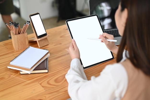 Kobieta pracująca z makietą komputera typu tablet i pusty ekran smartfona