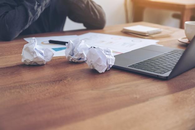 Kobieta pracująca z poczuciem porażki i zestresowana z pospieszanymi papierami i laptopem na stole w biurze