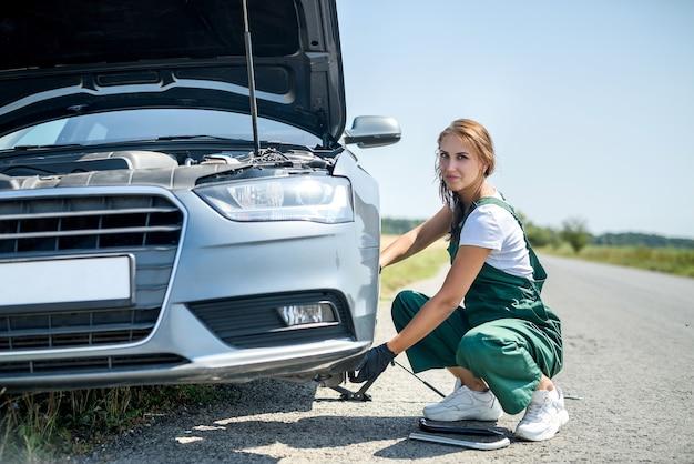 Kobieta pracująca z złamanym kołem swojego samochodu, czekająca na pomoc