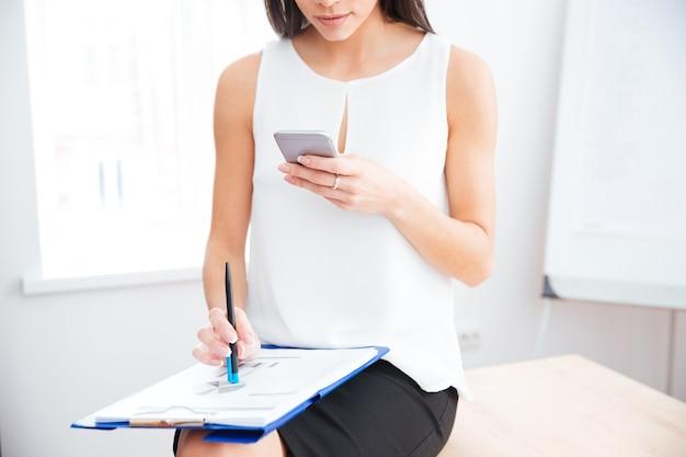 Kobieta pracująca ze smartfonem i dokumentami w biurze
