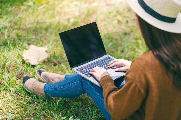 Kobieta pracuje i pisze na klawiaturze laptopa siedząc na zewnątrz